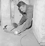 Chimney sweep crawling out of a chimney, Finland, 1958