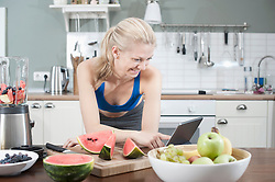 Young woman using digital tablet in the kitchen and smiling, Bavaria, Germany