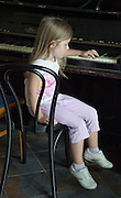 Thoughtful young girl age 8 plunking the piano keys. Zawady Central Poland