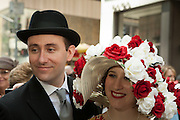 A couple in traditional outfits of the 1930s. He wears a homburg, and she a wide-brimmed straw covered in red and white roses.