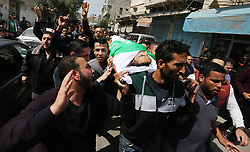 April 14, 2018 - Gaza City, Gaza Strip, Palestinian Territory - Mourners carry the body of Palestinian Islam Herzallah, 28, who was killed during clashes with Israeli security forces at the Israel-Gaza border during his funeral in Gaza City on April 14, 2018  (Credit Image: © Ashraf Amra/APA Images via ZUMA Wire)