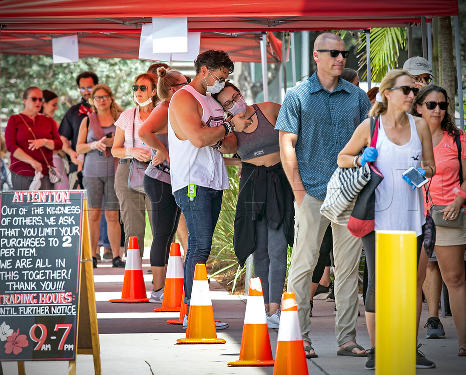 Valentina Watson leans on Gio Watson wearing face masks as they wait in line to enter Trader Joe's for grocery shopping at 9205 So. Dixie Highway in Miami on Tuesday, March 31, 2020.