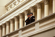 Beneath Corinthian pillars and columns, two Met Police officers keep a lookout from a balcony during the annual Trooping of the colour parade in the Mall. From their high vantagepoint, the two policemen watch spectator crowds as members of the armed services as they march past towards the nearby parade ground at Horseguards. Security is tight in an era of IRA terrorist activity in the early 1990s. The Sovereign's birthday is officially celebrated by the ceremony of Trooping the Colour on a Saturday in June.