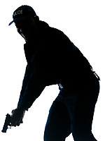 Silhouetted image of afro American policeman holding handgun in studio on white isolated background