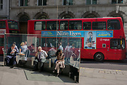 With a red London bus featuring a new film starring Kevin Spacey, City workers enjoy an unusual autumn heatwave from the shelter of a glass sreen on 13th September 2016, in the City of London, England.