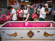 01 FEBRUARY 2017 - BANGKOK, THAILAND:  A man drops a donation into a coffin during Lunar New Year observances at the Poh Teck Tung Shrine in Bangkok. This is the Year of the Rooster in the Chinese zodiac and people pray and make merit to large statues of roosters in Chinese temples and shrines. Poh Teck Tung provides coffins for indigent people who can't afford them and donating money to Poh Teck Tung for coffins is a New Year's tradition in Bangkok.    PHOTO BY JACK KURTZ