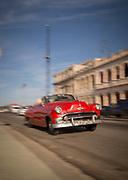 Vintage car driving along Malecon road between defocused buildings, Havana, Cuba