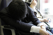deep sleeping young businessman and a casual dressed person during their train commute Japan Tokyo