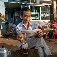 A man reads a newspaper at a small cafe in Ho Chi Minh City, Vietnam.