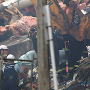 A dead body is removed from the rubble of the CTV building in Christchurch City Centre after a Powerful earth quake ripped through Christchurch, New Zealand on Tuesday lunch time killing at least 65 people as it brought down buildings, buckled roads and damaged churches and the Cities Cathedral. Photo Tim Clayton