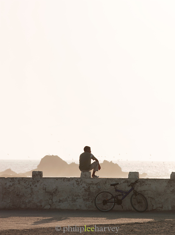 A young man sits on the sea wall at sunset near the dock at Essaouira in Morocco