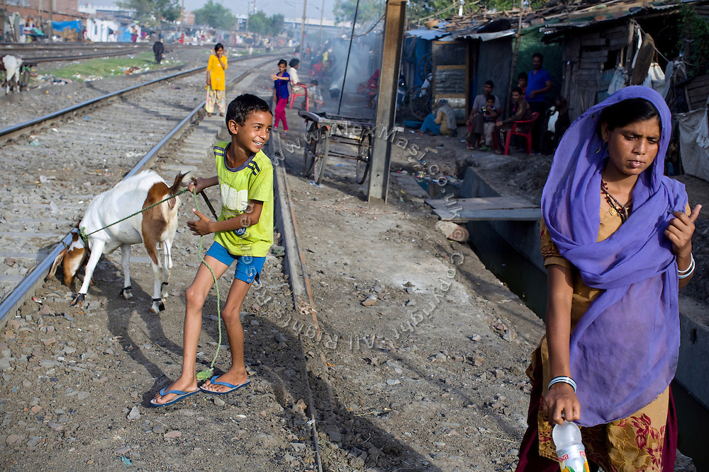 A boy is smiling while walking with his goat along the railway tracks in New Arif Nagar, one of the water-affected colonies standing next to the abandoned Union Carbide (now DOW Chemical) industrial complex, site of the infamous 1984 gas tragedy in Bhopal, Madhya Pradesh, central India. The poisonous cloud that enveloped Bhopal left everlasting consequences that today continue to consume people's lives.