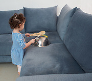 Toddler girl plays with household items such as pots and pans indoors