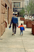 African American father and son ages 28 and 4 holding hands walking downtown.  Chicago Illinois USA
