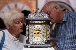 """© Licensed to London News Pictures. 28/06/2018. LONDON, UK. Visitors view """"an iconic silver basket ebony striking table clock"""", 1690, by Joseph Windmills. Members of the public visit Masterpiece London, the world's leading cross-collecting art fair held in the grounds of the Royal Hospital Chelsea.  The fair brings together 160 international exhibitors presenting works from antiquity to the present day and runs 28 June to 4 July 2018.  Photo credit: Stephen Chung/LNP"""