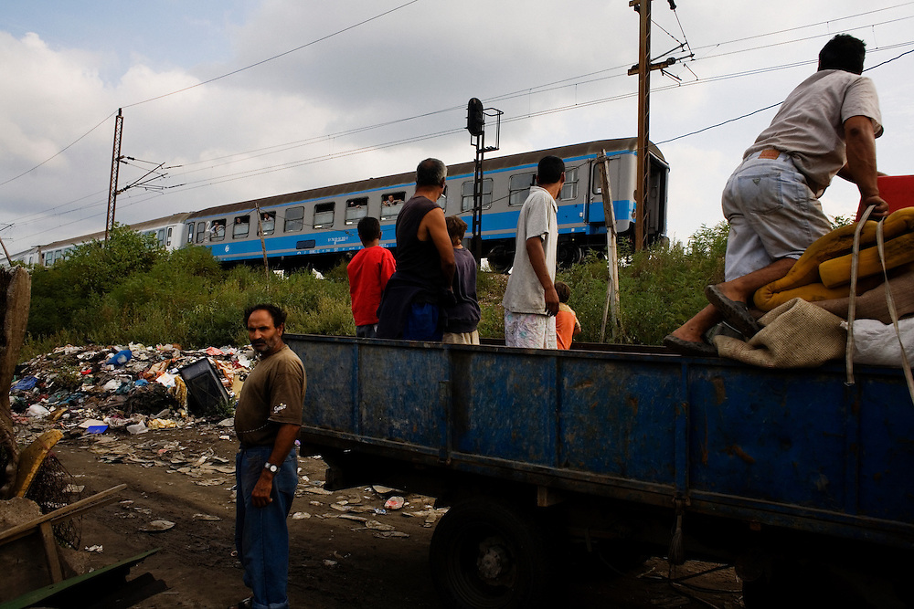 Men and boys load a truck with their belongings the day before relocation while a train passes above the camp. Nova Gazela.