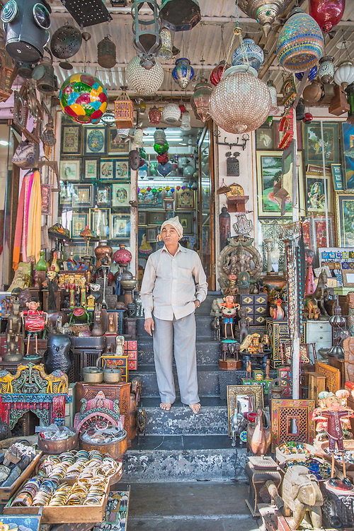 A shopkeeper stands for a photograph just outside Udaipur's City Palace, in Rajasthan, India.