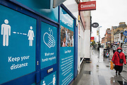 A member of the public wearing a face covering to help prevent the spread of the coronavirus passes COVID-19 public information displays on 4 October 2020 in Slough, United Kingdom. Slough Borough Council confirmed on 2nd October that its coronavirus infection rate is the highest in the south of England and Slough MP Tan Dhesi asked Health Secretary Matt Hancock in Parliament whether the local test centre in Montem Lane could be reverted to permit walk-in and drive-in visits without an appointment.