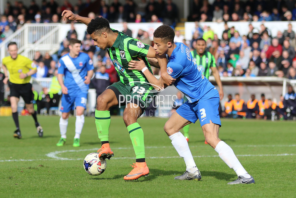 Lyle Taylor forward for AFC Wimbledon (33) shields the ball from Hartlepool United defender Jake Carroll (3) during the Sky Bet League 2 match between Hartlepool United and AFC Wimbledon at Victoria Park, Hartlepool, England on 25 March 2016. Photo by Stuart Butcher.