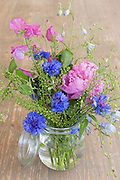 Posy bunch of pretty attractive pink and blue spring and summer flowers, a rustic floral bouquet arrangement in glass kilner style vase jar