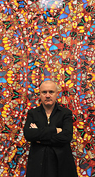 © Licensed to London News Pictures. 02/04/2012. London, UK . Damien Hirst is photographed as he stands in front of 'I Am Become Death, Shatterer of Worlds 2006'. The Tate Modern presents the first substantial retrospective of British artist Damien Hirst. The exhibition tuns 4th April - 9th September at Tate Modern London. Photographers Stephen Simpson/LNP
