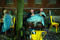 © Licensed to London News Pictures. 12/04/2021. Manchester, UK. Two men share a blanket to stay warm outside a bar on Canal Street . People on a night out in Manchester City Centre as government restrictions to control the spread of Coronavirus are eased across the UK. Pubs, restaurants, hairdressers, gyms and non essential retailers are now permitted to serve customers within restrictions. Photo credit: Joel Goodman/LNP