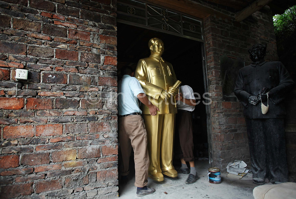 """Workers move a statue of Mao Zedong at the workshop of a """"Red"""" memorabilia collector and manufacturer, near Mao's birthplace in Shaoshan, Hunan Province, China on 12 August 2009.  The workers were once electricians. The village of Shaoshan, in rural Hunan Province, is tiny in size but big in name. It was the childhood home for Mao Zedong, the controversial revolutionary who came from obscurity but eventually defied all odds conquered China in the name of communism. Now his home, a sacred place among China's official propaganda, is in reality a microcosm of the country itself: part commercialism, part superstition, with a dash of communist ideological flavor."""