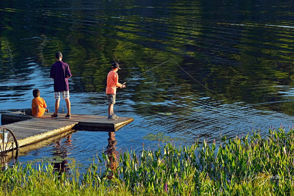 Boys on a dock fishing, Wanup, Ontario, Canada