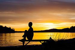 February 10, 2016 - Woman practising yoga by lake at sunset (Credit Image: © Image Source via ZUMA Press)