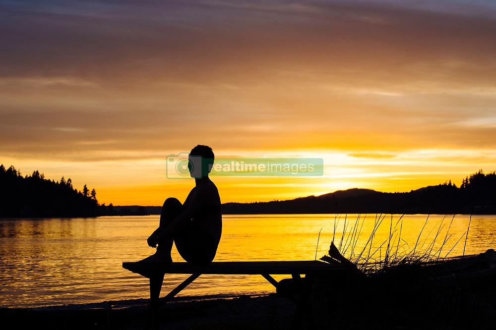 February 10, 2016 - Woman practising yoga by lake at sunset (Credit Image: © Image Source via ZUMA Press)