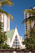 Saint Augustine Church rises between the buildings in Waikiki.