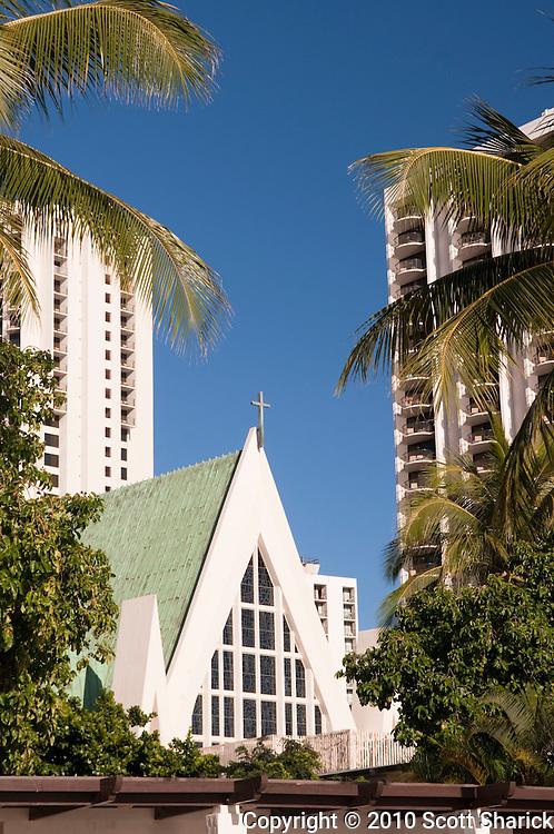 Saint Augustine Church rises between the buildings in Waikiki.
