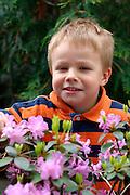 Happy adventurous boy age 5 in family garden.  St Paul Minnesota USA