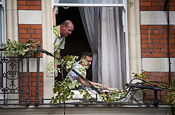 © Licensed to London News Pictures. 20/09/2018. London, UK. Workmen assess damage at the scene where a tree has been blown over in high winds in Kensington, West London, hitting a residential building, causing damage and breaking a window. Parts of the UK have been battered by Storm Ali.Photo credit: Ben Cawthra/LNP