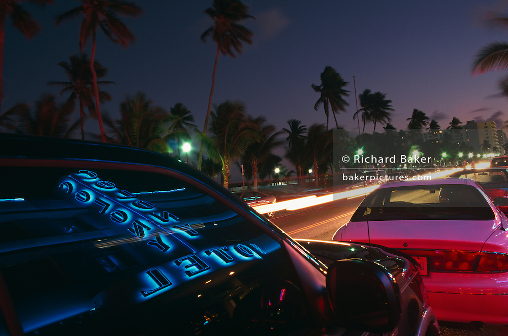 During a time-exposure of a few seconds, the ambient neon and natural evening light of Miami Beach's Ocean Drive are mixed together to give an atmospheric mood of vitality, bustle and excitement in this tropical city. The vertical-aligned name of the famous Colony Hotel is seen through the darkened window of an SUV (4x4). Glowing pinks and blues are vivid in this scene where beautiful people and expensive cars cruise along slowly, each parading bodywork and personality. Palm trees sway about in the coastal breeze, blurring during the exposure and making them ghostly against the fading sky of early evening. This is vibrant district of Miami, Florida. The place to hang-out and be noticed.