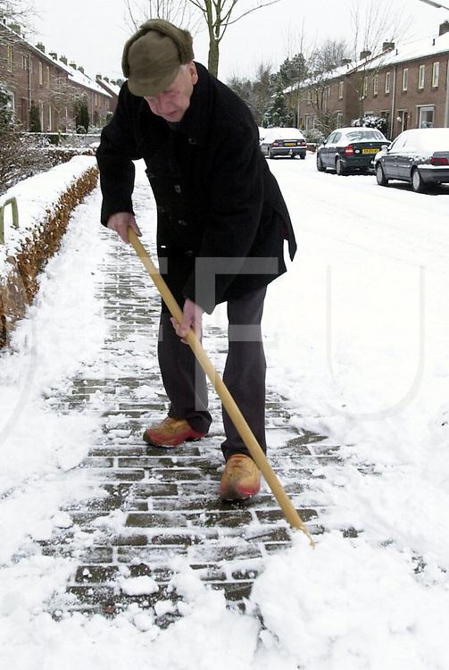 fotografie frank uijlenbroek©2001 michiel van de velde.011227 dalfsen ned.Winter in Salland>.Menigeen vergeet het, maar er rust een plicht op elke burger om zijn stoep ijs en sneeuwvrij te maken..De oudere generatie weet dat en dhr. Melenhorst houd zijn stoep  dan ook schoon.