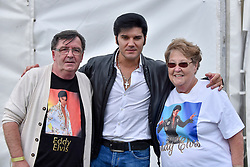 """© Licensed to London News Pictures. 23/07/2017. London, UK. Fans meet Eddy Popescu, an Elvis tribute singer.  Fans attend the capital's first ever """"Elvis Fest"""" to mark the 40th anniversary of the King of Rock N' Roll's death.  Taking place in Parsloes Park, Dagenham, the festival includes a variety of tribute acts representing Elvis through his career. Photo credit : Stephen Chung/LNP"""