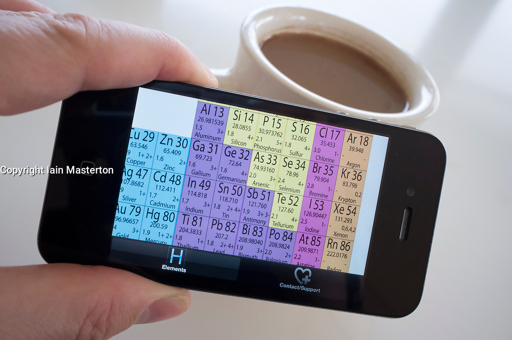 Student looking at periodic table of the elements on an iPhone 4G smart phone