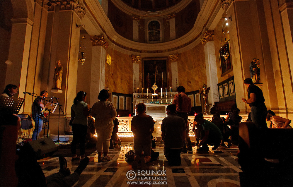 London, United Kingdom - 10 August 2012.Invited in by the catholic Nightfever team on the streets of Soho, members of the public light candles at St Patrick's Catholic Church, Soho Square, Soho, London, England, UK..Contact: Equinox News Pictures Ltd. +448700780000 - Copyright: ©2012 Equinox Licensing Ltd. - www.newspics.com.Date Taken: 20120810 - Time Taken: 213737+0000