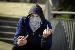 © Licensed to London News Pictures . 10/08/2011 . Manchester , UK . A young man on Deansgate , with his face covered , shows his middle fingers , as disorder spreads to Manchester during a 4th night of rioting and looting , following a protest against the police shooting of Mark Duggan in Tottenham . Photo credit : Joel Goodman/LNP