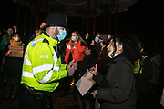 Hundreds of people gathered  at a peaceful vigil for Sarah Everard on Clapham Common in South London on the 13th of March 2021, London, United Kingdom. Sarah Everard went missing on 3 March after setting off at 9pm from a friend's house to make her two and a half mile journey home. A police man try in vain to jsutify their handling of the event and the arrests made. The vigil was also a call to end violence against girls and women perpetrated by men. The vigil was not sanctioned by police because of Covid restrictions and the police decided to arrest a number of people in an attempt to end the peaceful and highly emotional vigil. The event took place at the band stand on the common and speeches were held from the stand till police confiscated the sound equipment.