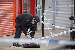 © Licensed to London News Pictures. 11/05/2021. London, UK. Police guard a crime scene in Dollis Hill in North West London after reports of a shooting. Local media are reporting that person was rushed to hospital after an Ambulance was called at 1:52pm. A police cordon is in place on Dudden Hill Lane and on Cooper Road. Photo credit: Marcin Nowak/LNP