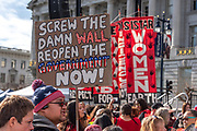 """San Francisco, USA. 19th January, 2019. The Women's March San Francisco begins with a rally at Civic Center Plaza in front of City Hall. During the rally, a man holds a sign criticizing Trump's wall and the shutdown, reading """"Screw the damn wall. Reopen the government now!"""" Credit: Shelly Rivoli/Alamy Live News"""