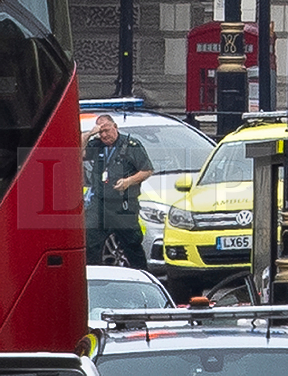© Licensed to London News Pictures. 14/08/2018. London, UK. An ambulance worker passes near the silver car that crashed into barriers outside Parliament. A number of pedestrians are injured. The driver was arrested.  Photo credit: Peter Macdiarmid/LNP