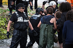 Denham, UK. 24 July, 2020. Enforcement agents from the National Eviction Team intervene as environmental activists from HS2 Rebellion try to protect an ancient alder tree from destruction in connection with works for the HS2 high-speed rail link in Denham Country Park. A large policing operation involving the Metropolitan Police, Thames Valley Police, City of London Police and Hampshire Police as well as the National Eviction Team was put in place to enable HS2 to remove the tree.