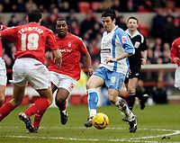 Photo: Leigh Quinnell.<br /> Nottingham Forest v Swindon Town. Coca Cola League 1. 25/02/2006. Swindons Lee Peacock is watched by Nottingham Forests Wes Morgan and John Thompson.