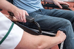Occupational Therapist measuring a wheelchair user for size