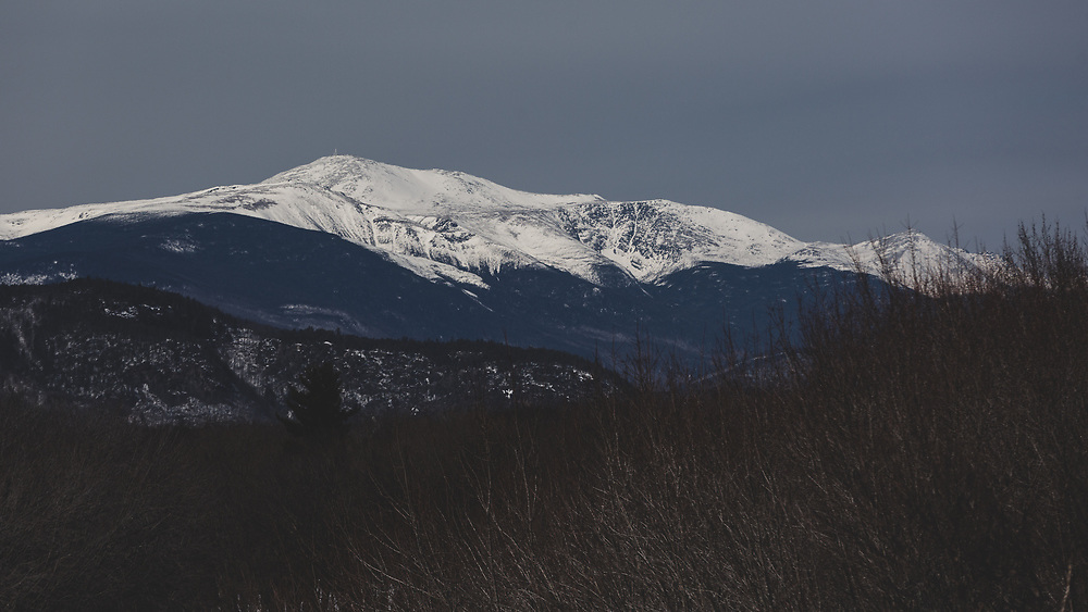 A snow covered Mount Washington seen in the distance from the foothills of New Hampshire's White Mountains on a cold winter afternoon.