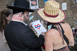 © Licensed to London News Pictures. 20/06/2017. London, UK. A jewish man holds a piece of paper with 'Finsbury Park #we stand together' printed on it near Finsbury Mosque in north London after a van ploughed into a crowd nearby. One person has been killed and 10 people are injured. Darren Osborne, 47, from Cardiff, continues to be held on suspicion of attempted murder and alleged terror offences.  Photo credit: Peter Macdiarmid/LNP