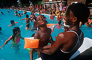 A 1990s Afro-Caribbean mother and her child enjoy the August heatwave in the unheated waters of the Grade II listed  Brockwell Brixton Lido in Brockwell Park, Herne Hill, 25th August 1995, in London, England. The Lido is an oasis for city dwellers to escape, if only for an hour from the pressures of fast urban life. Brockwell Lido is a large, open air swimming pool in Brockwell Park, Herne Hill, London. It opened in July 1937, closed in 1990 but after a local campaign was re-opened in 1994. Brockwell Lido was designed by HA Rowbotham and TL Smithson of the London County Councils Parks Department to replace Brockwell Park bathing pond.